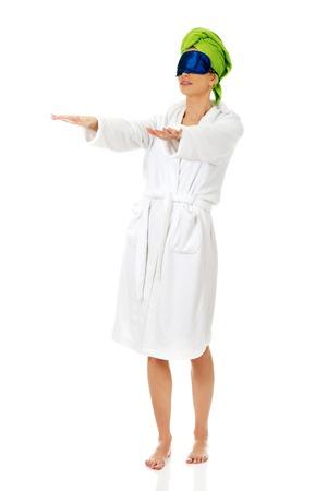 Sleepwalking woman in bathrobe and sleep bandage.