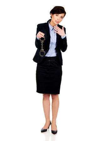metal handcuffs: Guilty businesswoman holding metal handcuffs.