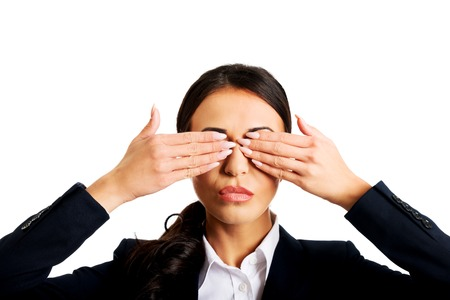 hands covering eyes: Young businesswoman covering eyes with hands. Stock Photo