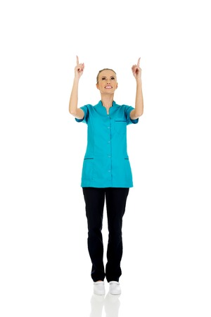 pointing up: Beautiful female doctor pointing up. Stock Photo