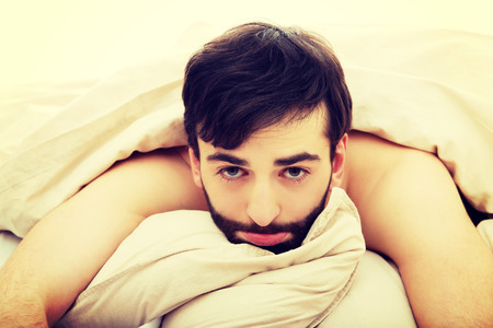wakening: Young man waking up in his bedroom.