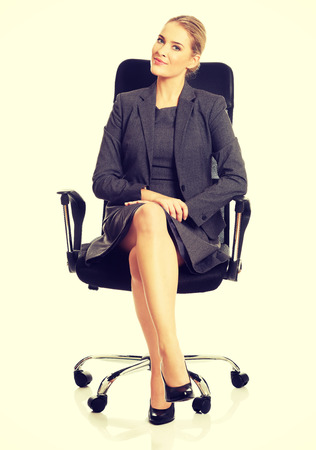 comfortable chair: Beautiful businesswoman sitting on armchair