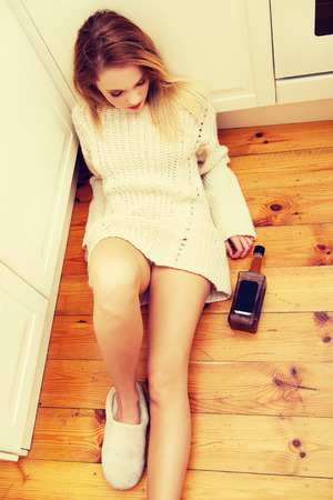solter�a: Triste joven borracho sentado en la cocina en casa.
