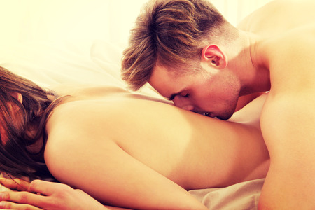 man and woman sex: Man kissing woman in her back on bed. Stock Photo