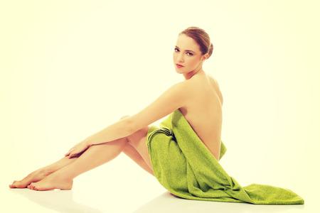 mujer desnuda sentada: Spa joven hermosa mujer sentado envuelto con una toalla.