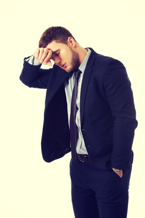 worried businessman: Handsome worried businessman touching his forehead. Stock Photo