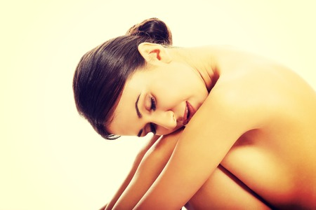 seins nus: Calme femme aux seins nus assis avec sa tête sur les genoux. Banque d'images