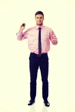 Young handsome businessman holding billiard ball. photo