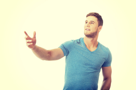 man pointing up: Handsome young casual man pointing up.