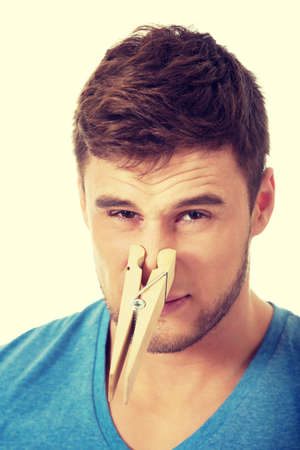 stinks: Young handsome man with clothespin on his nose.
