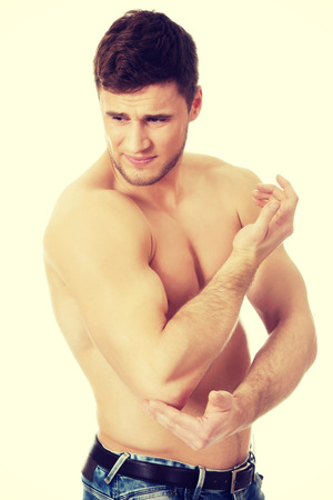 elbow pain: Handsome athletic man suffering from elbow pain.