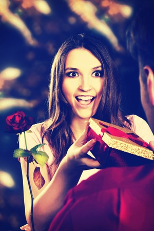 recieving: Shocked woman recieving a gift on Valentines Day.