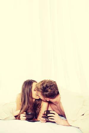 amantes en la cama: Joven pareja feliz besar y beber café en la cama.