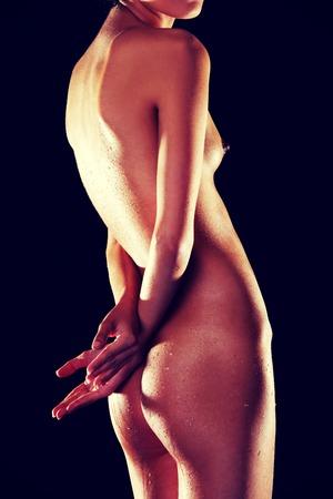 naked female body: Side view naked female body on a dark background.