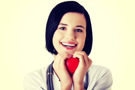 Portrait of female doctor holding heart model. photo