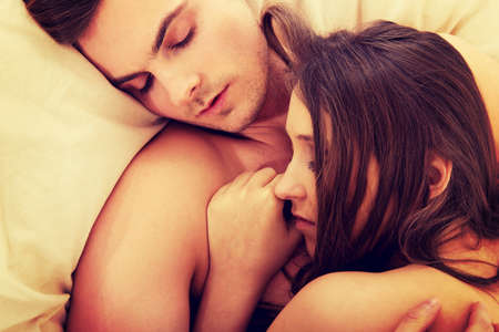 nude young: Loving affectionate nude heterosexual couple relaxing in bed.