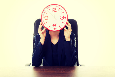 big behind: Businesswoman sitting at the desk hiding behind big clock Stock Photo