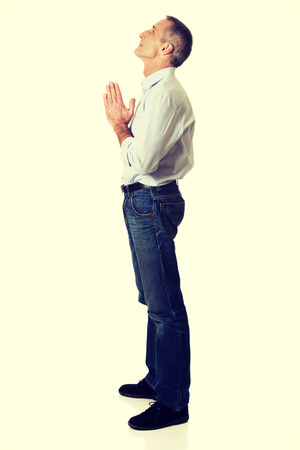 implore: Full length side view of a man praying to God.