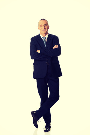 folded arms: Mature confident businessman standing with folded arms. Stock Photo
