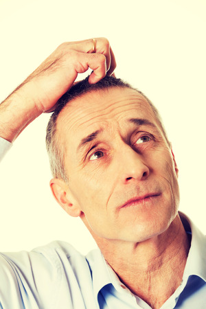 raised eyebrows: Mature confused man scratching his head. Stock Photo
