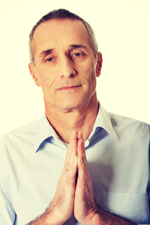 to implore: Handsome mature man praying to God. Stock Photo