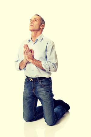 man kneeling: Man kneeling and praying to God. Stock Photo