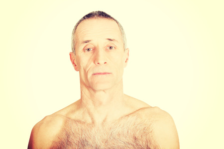Serious shirtless old man looking at camera photo