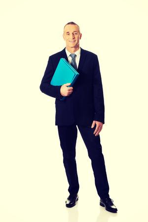 full length: Full length mature businessman holding a binder. Stock Photo