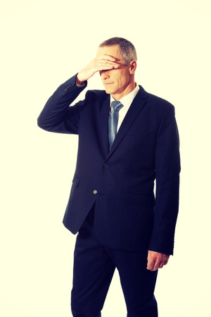 blunder: Stressed businessman covering his face.