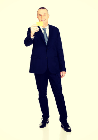 full length: Full length businessman showing a yellow card.