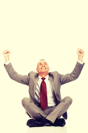 crosslegged: Cheerful businessman sitting cross-legged on the floor.