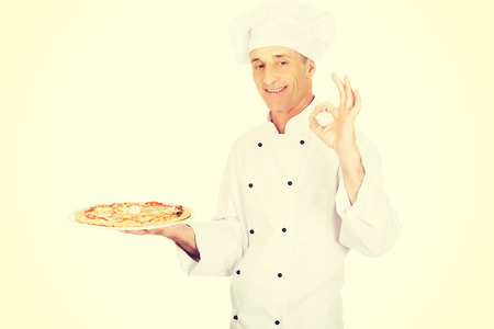 perfect sign: Chef baker with italian pizza on plate showing perfect sign.