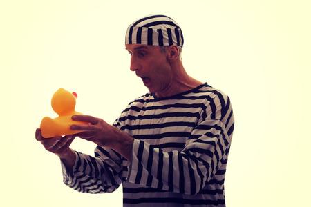 pato de hule: Hombre triste prisionero maduro criminal con pato de goma. Foto de archivo