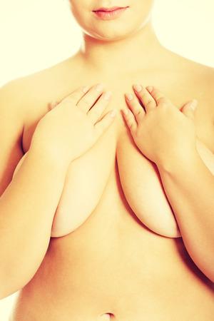 mujeres desnudas: Mujer gorda que cubre su pecho