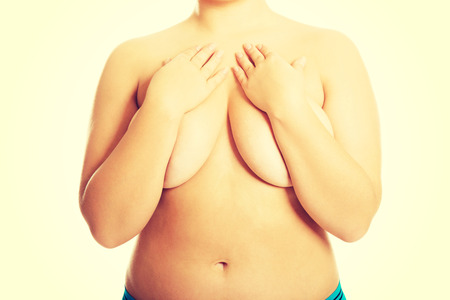 mujeres jovenes desnudas: Mujer con sobrepeso que cubre su pecho.