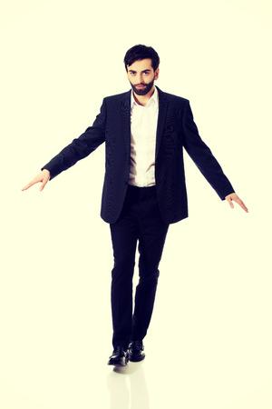 carefully: Businessman walking carefully, try to balance himself.