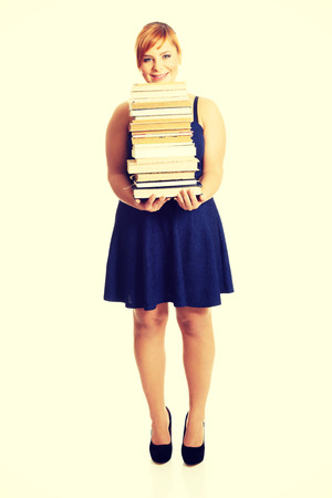 overweight students: Overweight woman in skirt holding heavy books