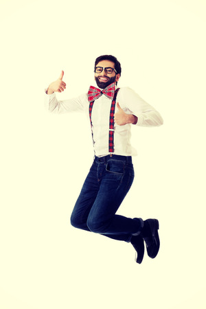 Funny man wearing suspenders jumping with thumbs up. photo