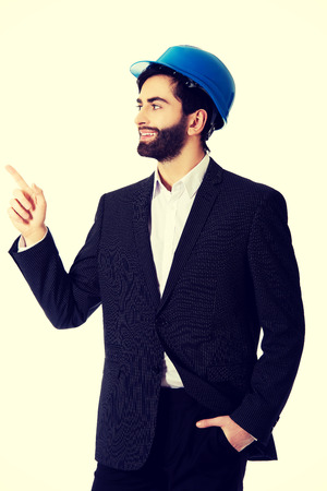 Smiling handsome businessman with hard hat pointing up. photo