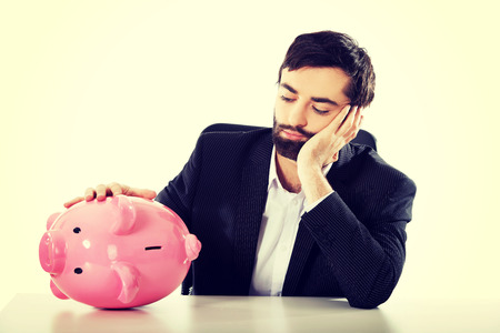 worried businessman: Worried businessman with piggybank by a desk. Stock Photo