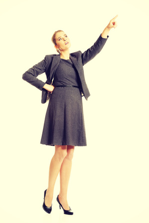 pointing up: Businesswoman pointing up on space