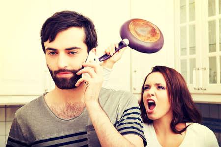 divorcio: Mujer joven que golpea su rabia hablando socio con el sartén.