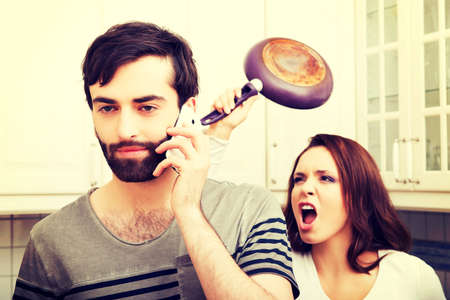 stunned: Young rage woman hitting her talking partner with frying pan. Stock Photo