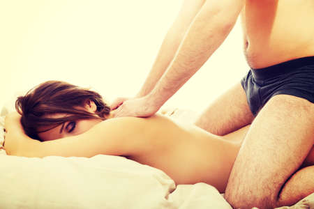 male massage: Relaxing young couple making massage at home. Stock Photo
