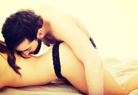 foreplay: Young beautiful couple having foreplay in bedroom.