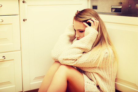 lonliness: Sad lonely young woman sitting in the kitchen at home.