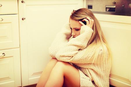 solter�a: Triste joven solitaria sentado en la cocina en casa.
