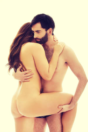 adult nude: Handsome man embracing naked woman and holding her leg.