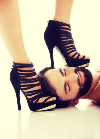 Sexy womans foot in high heel on mans face, dominating him. Stock Photo