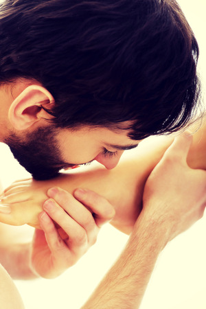 feet naked: Handsome young man kissing womans bare feet.